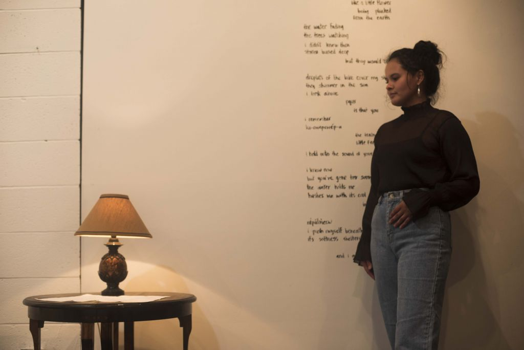 Image of the artist standing in a gallery against a wall of poetry.